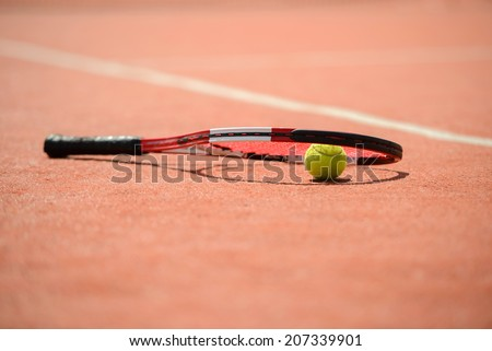 View of tennis racket and balls on the clay tennis court