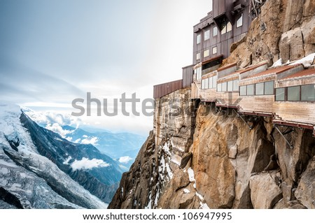 View of the Alps from Aiguille du Midi mountain in the Mont Blanc massif in the French Alps. Summit tourist station in foreground. Alps, France, Europe. - stock photo