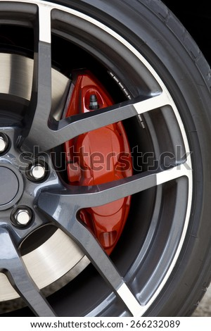 View of the aluminum wheel of a sport car with red brake caliper. Red brake caliper.