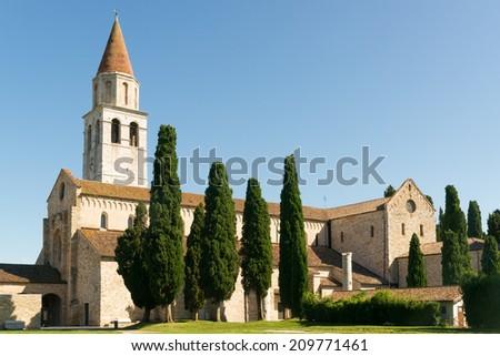 View of the ancient Basilica di Santa Maria Assunta in Aquileia against a blue sky - stock photo