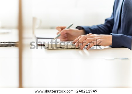 View of the arms of a businesswoman sitting working at her desk in the office checking and analysing a report with copyspace on a white desk top. - stock photo