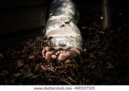 View of the bare feet of the wrapped body of a homicide victim lying in leafy detritus in the darkness in a conceptual image of violence and crime - stock photo