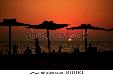 view of the beach at sunset with silhouettes of people's leisure and sun umbrellas