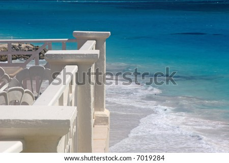 View of the beach below from a tropical balcony.