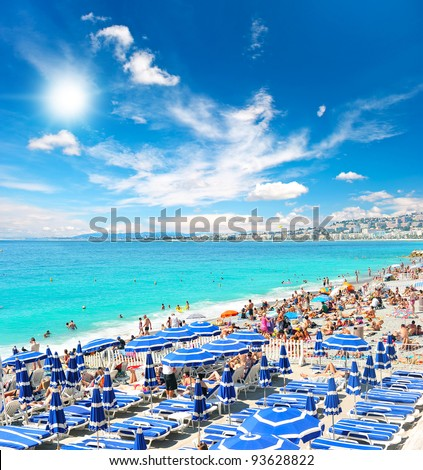 View of the beach in Nice, France, near the Promenade des Anglais, full with tourists, sunbeds and umbrellas on summer hot day