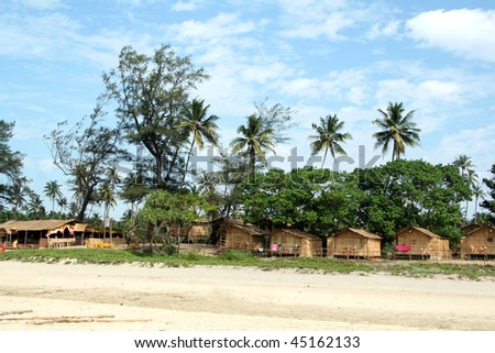 View of the beach with coconut palms and bungalows - stock photo