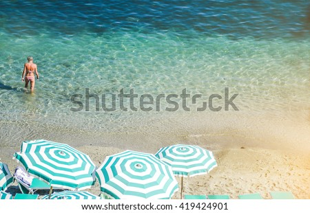 view of the beach with umbrellas and a young woman who is walking in the water - lifestyle,people, nature and landscpae concept - stock photo