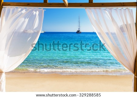 View of the beautiful beach through a Balinese bed - stock photo