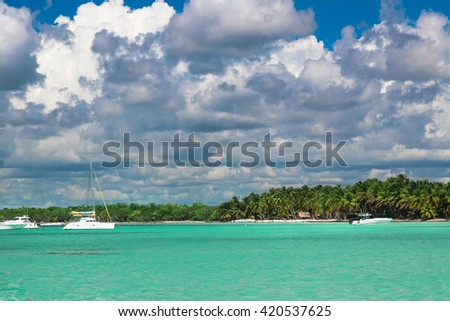 View of the beautiful sail boat or yacht docked next to green island. - stock photo