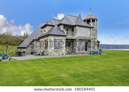 VIew of the big stone house with concrete floor patio area. - stock photo