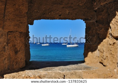 View of the boat and the sea from the window-slits of the fortress walls, Rhodes, Greece