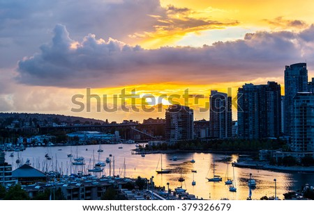 view of the buildings of vancouver city skyline and a marina during a beautiful sunset