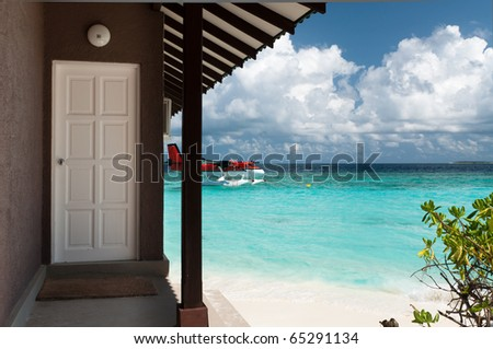 View of the bungalows on the beach and the seaplane. - stock photo