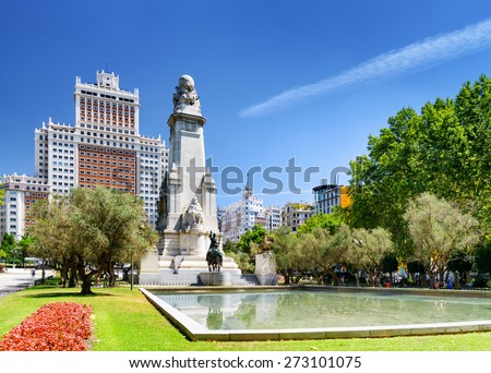 View of the Cervantes monument and the Spain Building (Edificio Espana) on the Square of Spain (Plaza de Espana) on the blue sky background in Madrid. Madrid is popular tourist destination of Europe. - stock photo