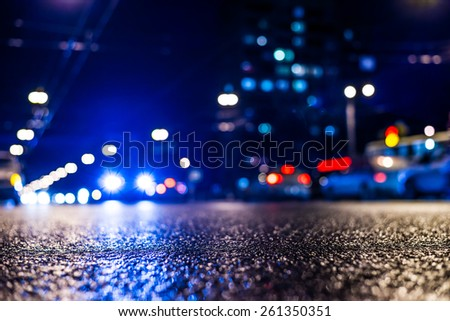 View of the city at night after the rain, the cars driving on the road and shine the headlights. View from the level of asphalt level, in blue tones - stock photo