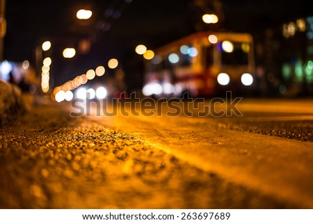 View of the city at night, the cars and tram driving on the road. View from the level of asphalt level - stock photo