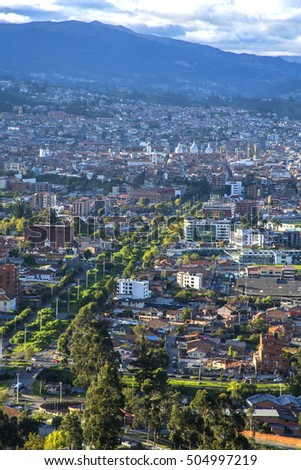 View of the city of Cuenca, Ecuador, with it's many churches and rooftops, on a cloudy and sunny day