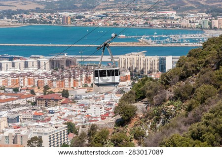 View of the city of Gibraltar and cable car close to the top of Gibraltar rock - stock photo