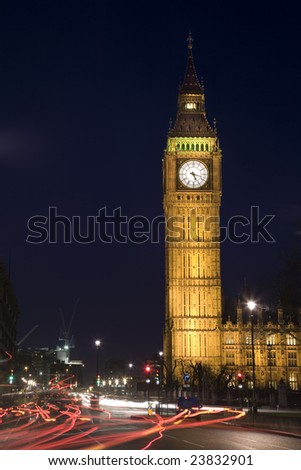 View of the clock tower of the Houses of Parliament (Westminster Palace) at Night, with traffic trails in the foreground
