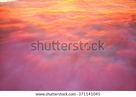 View of the cloudscape from the plane window at sunset. - stock photo