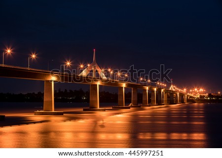 View of the concrete bridge with golden light reflection on water surface at night time