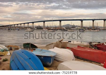 View of the Coronado Bay Bridge and shoreline boats at sunset in San Diego, California. - stock photo