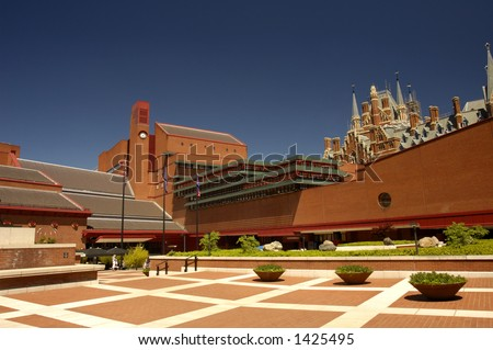 View of the courtyard of the british Library, London, with the gothic towers of St Pancras Station peeping over the top at the right. Space for text in the clear blue sky. - stock photo