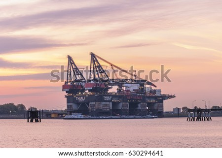 View of the crane ship Thialf  during Sunrise with pink orange clouds, a large deep water construction vessel from Heerema, builder of offshore platforms. Rotterdam  Europoort Netherlands April 2017