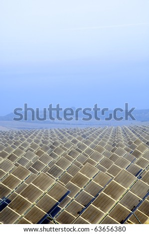 view of the dawn of a solar field with hills in the background - stock photo