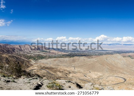 view of the desert valley from the top of a mountain in southern California, and to road to get to the top. - stock photo