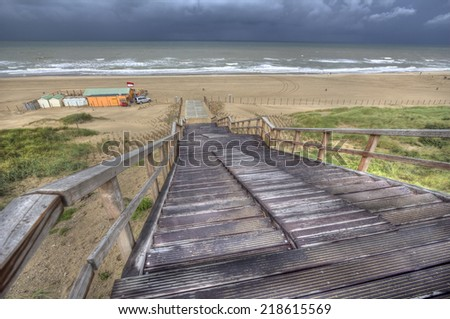 View of the dunes and North Sea from the top of a wooden staircase during a spell of bad weather in Holland - stock photo