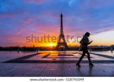 View of the Eiffel tower at sunset with a moving silhouette of a woman, Paris.