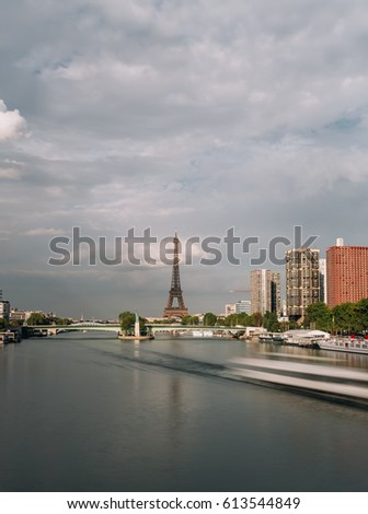 View of the Eiffel tower close to the Seine river and residential district in Paris, France. Famous touristic places and romantic travel destinations in Europe. Long exposure. Toned