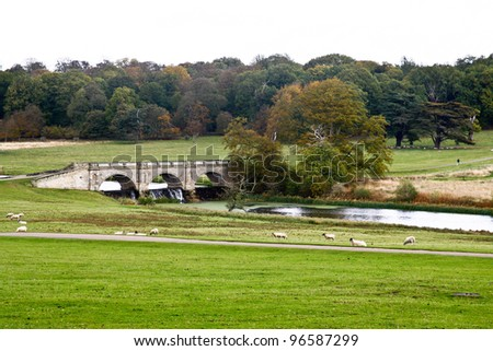 view of the english countryside with trees and a lush grass with a river flowing through the middle and a bridge crossing it. - stock photo