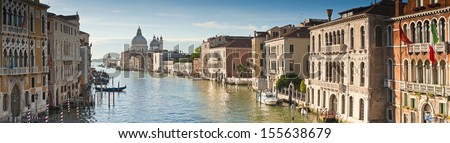 View of the Grand Canal and the stunning baroque Santa Maria Della Salute (1687) church in Venice and colourful villas bathed in early morning light. Stitched panoramic image. - stock photo