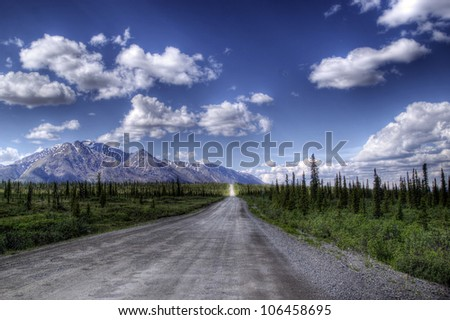 View of the gravel road called the Denali Highway going from Cantwell to Paxton in Alaska in summer with puffy clouds and spruce trees. - stock photo