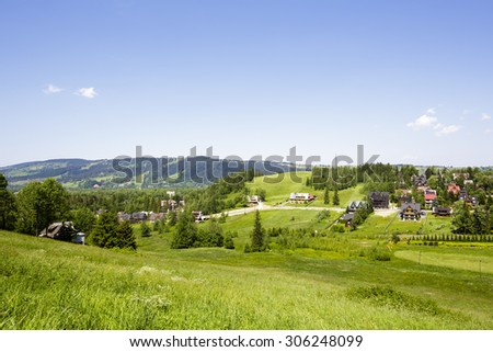 View of the green areas, a few residential buildings and in the distance visible hill called Gubalowka, shows the beauty of through a completely vegetated part of the city of Zakopane - stock photo