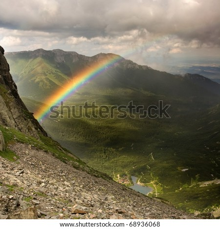 View of the green mountains, valley, lake, mountain hut, and a rainbow. Slovakian Tatra Mountains. - stock photo