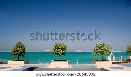 View of the Gulf of the coast of Abu Dhabi framed by a trio of trees - stock photo