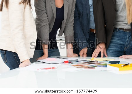 View of the hands of a group of business people selecting material for a project standing around a table on which it is displayed - stock photo