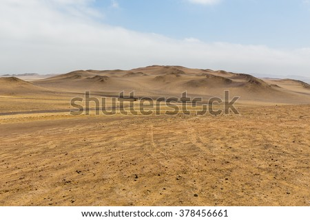 View of the highest sand dunes in the distance in the desert of the Paracas reserve in hot weather with haze in the air and cloudy skies - stock photo