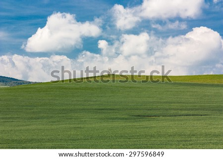 View of the hill. Stretching to the horizon, meadows and cultivated fields. In the distance, a lonely pulpit in the middle of the observation. Country: Poland, Location: Mountains Kaczawskie