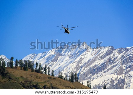 View of the Himalayas with departing behind the mountain the helicopter.