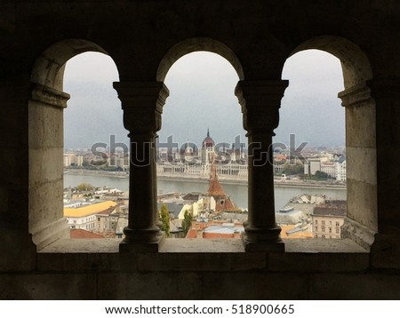 View of the Hungarian parliament building in Budapest through classical windows in the old town.