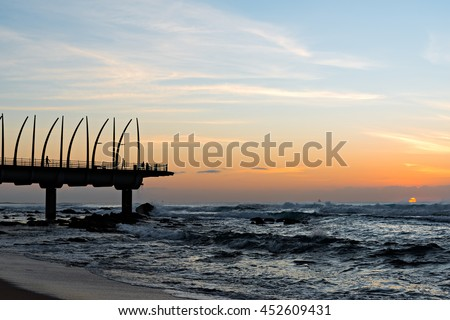 View of the Indian Ocean through the Millennium Pier in Umhlanga Rocks at Sunrise - stock photo