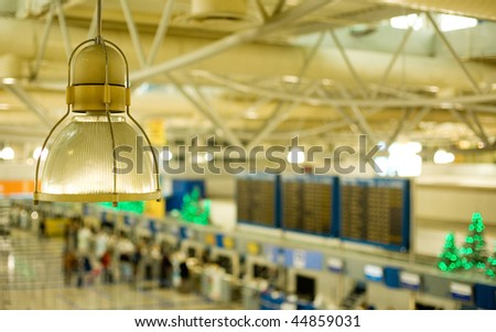 View of the international airport of Athens, Greece, with check-in counters, arrivals/departures board and decorated Christmas trees. Focus is on the lamp - stock photo