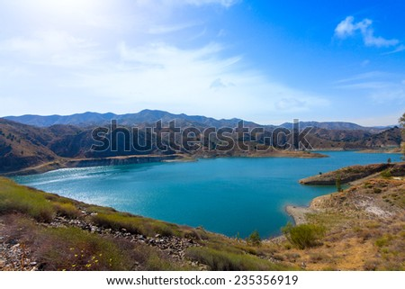 View of the lake and surrounding countryside at El Limonero reservoir, Malaga, Spain - stock photo