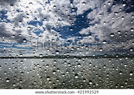 View of the lake storm through the window glass covered by raindrops