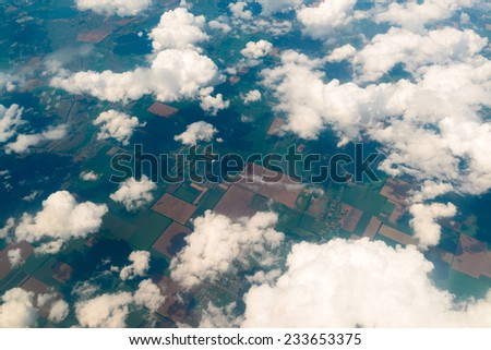 View of the land, fields, and clouds from above - stock photo
