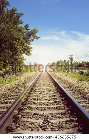 "view of the length of railway with green tree at left and right side of railway,filtered image, light effect and flare added,selective focus,mean ""There light at the end of the tunnel"", success way